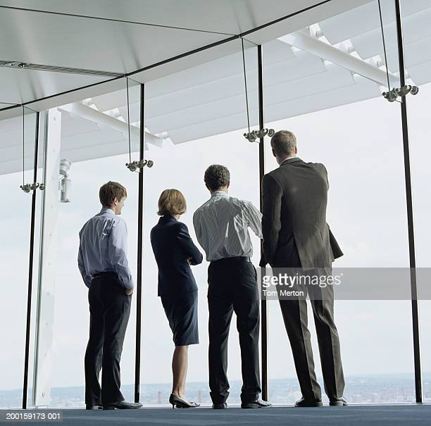 Four business colleagues looking out of office window, rear view
