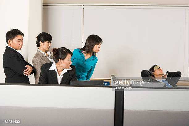 Four business executives looking at their colleague napping on a chair in an office