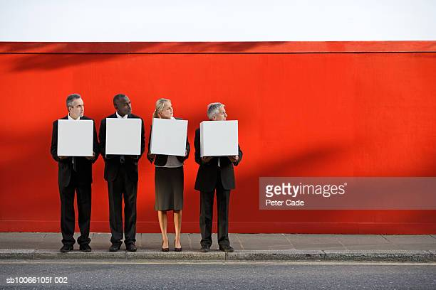 Four business executives standing holding white boxes in front of red wall
