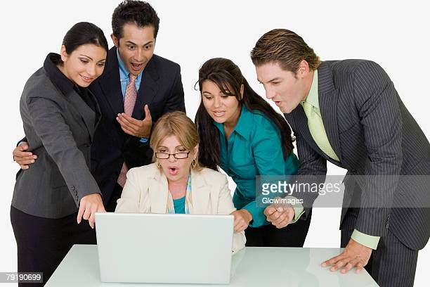 Four business executives surrounding a businesswoman working on a laptop