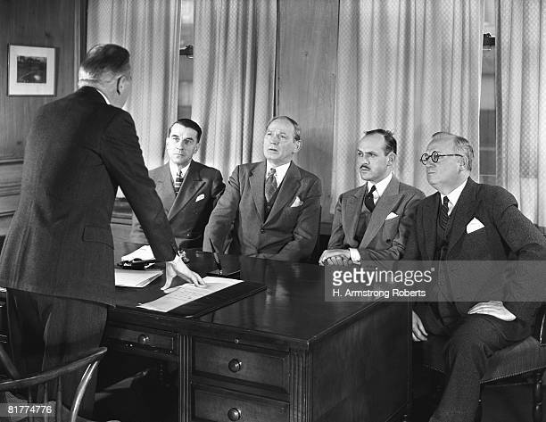 Four business men sitting around desk in paneled office, listening to fifth man speaking.