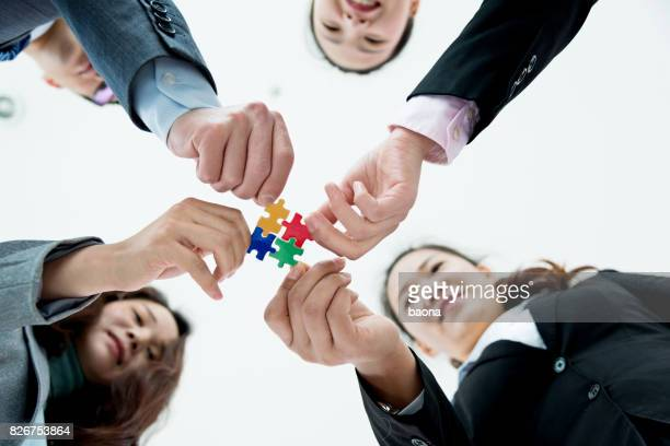Four business people holding puzzle pieces