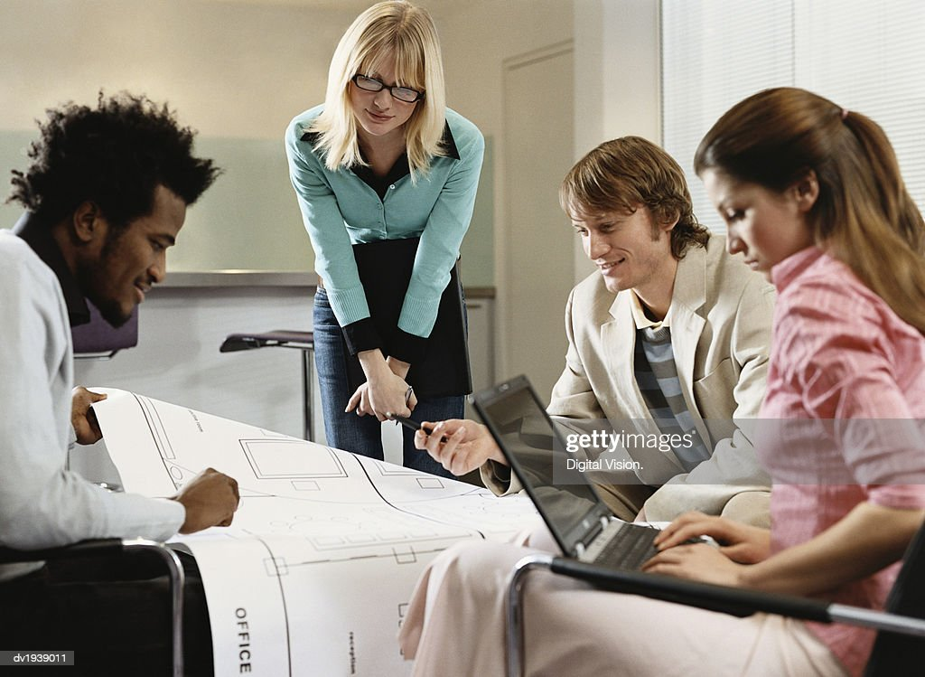 Four Business People in a Meeting Looking at a Blueprint : Stock Photo
