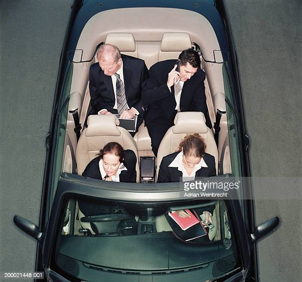 Four business people in open top car, elevated view