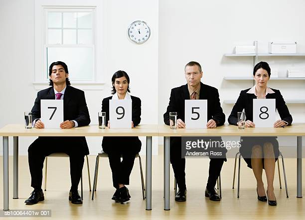 four business people sitting at desk, holding score cards, portrait - scoring stock pictures, royalty-free photos & images