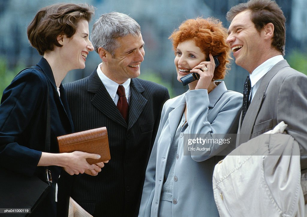 Four business people standing outside smiling, businesswoman on cell phone : Stockfoto