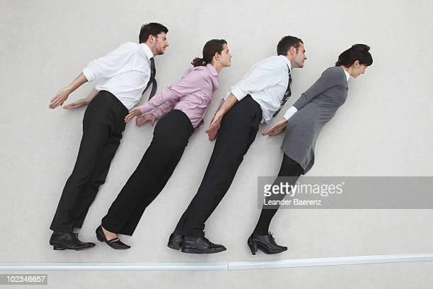 four business people standing side by side, side view, elevated view - aerodinâmico - fotografias e filmes do acervo