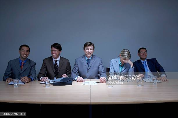 Four businessmen and businesswoman at boardroom table, smiling