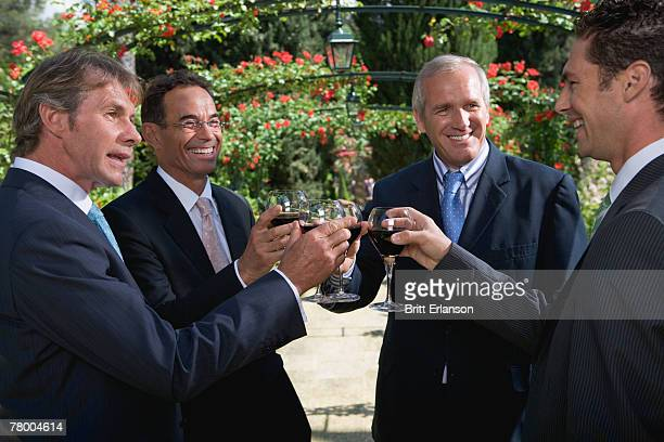 Four businessmen drinking wine in a garden