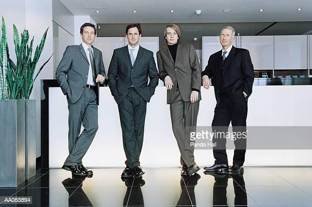 four businessmen leaning on counter, portrait - abbigliamento da lavoro formale foto e immagini stock