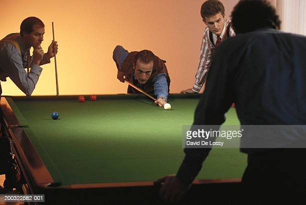 Four businessmen playing billiards