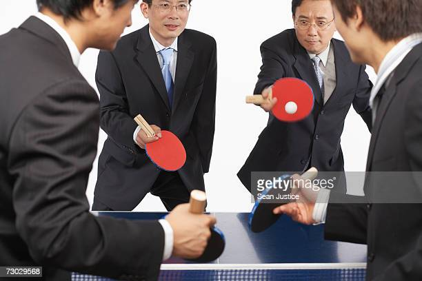 Four businessmen playing table tennis