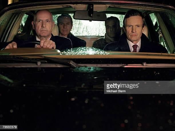 Four businessmen sitting in car