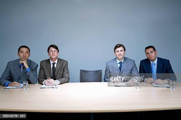 Four businessmen sitting next to empty chair in boardroom, portrait