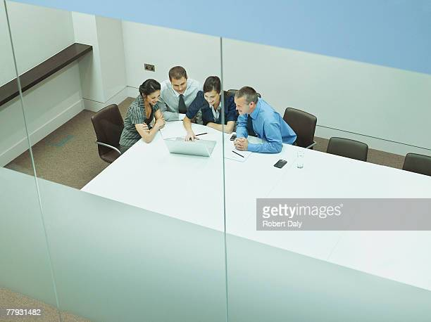 four businesspeople at a table with documents and laptop - four people stock pictures, royalty-free photos & images