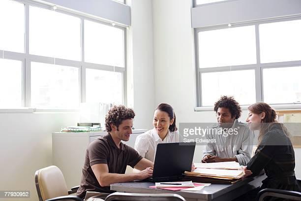 Vier Geschäftsleute in einem Büro arbeiten