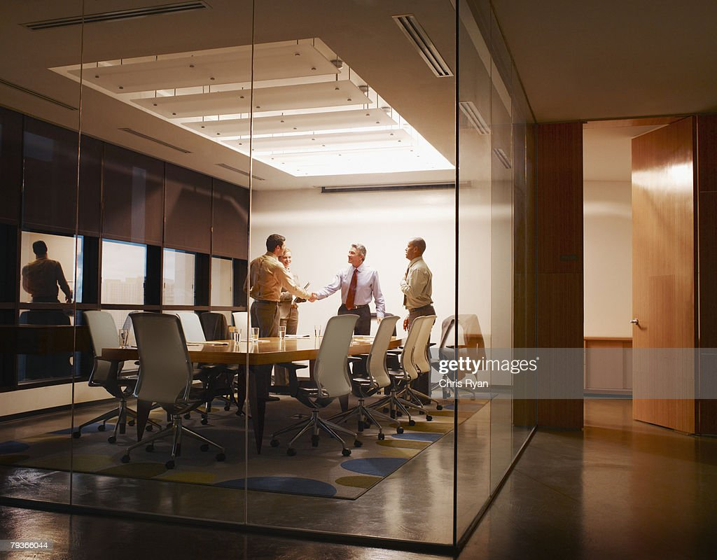 Four businesspeople in boardroom with two shaking hands : Stockfoto