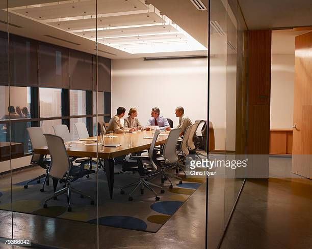 Four businesspeople in boardroom working