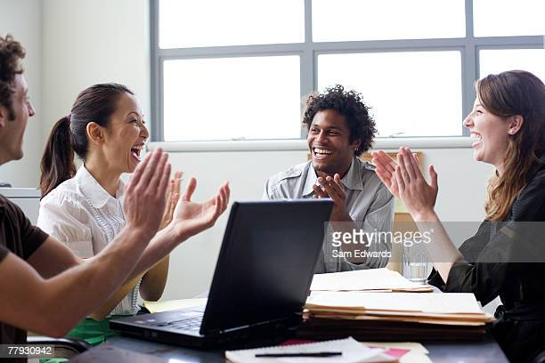 Four businesspeople in office applauding
