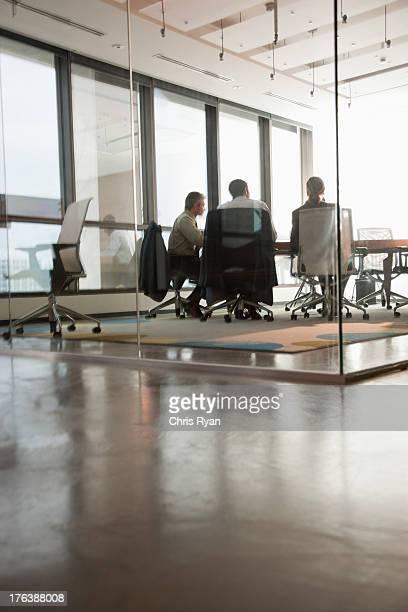 quatro empresários sentado em uma mesa de sala de reuniões - vertical imagens e fotografias de stock