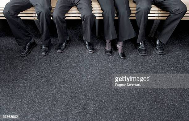 Four businesspeople sitting on a bench