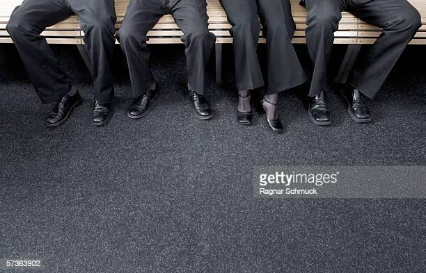 four businesspeople sitting on a bench - schwarze schuhe stock-fotos und bilder