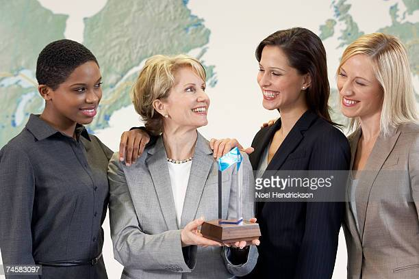 Four businesswomen standing in front of wall map of North America and Europe, one holding trophy, group portrait