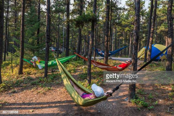 Four campers relax in hammocks, at campground