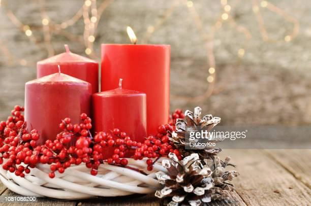 four candles in a white wreath with red berries on a wooden rustic background with lights. advent calendar for christmas. - advent calendar stock photos and pictures