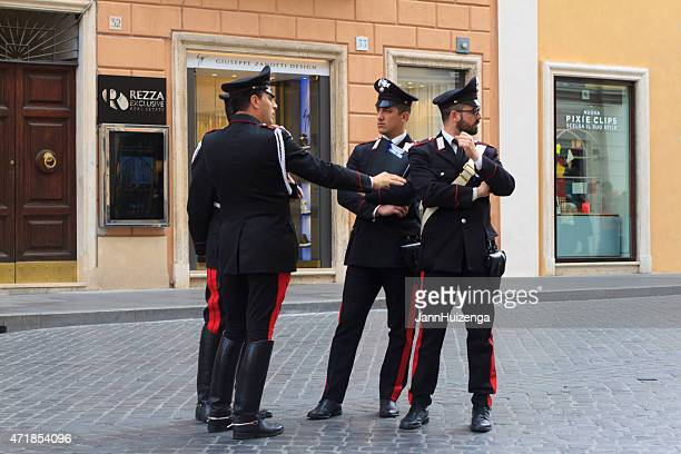 Four Carabinieri Officers Chatting on Cobbled Street in Rome, Italy