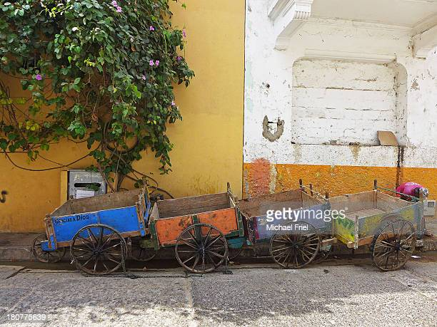 Four chained and colorfully-painted traders' carts are lined up in an old street in historical Cartagena, Colombia
