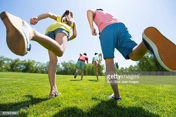 Four cheerful young adults running on grass
