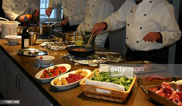 Four chefs at a table with various cookware and food items