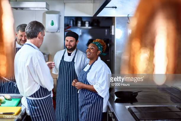 four chefs chatting in commercial kitchen - restaurant stock pictures, royalty-free photos & images