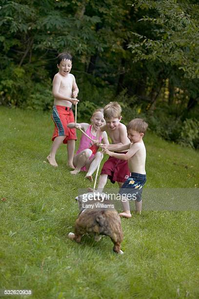 Four Children and Bulldog Playing with Rope Outdoors