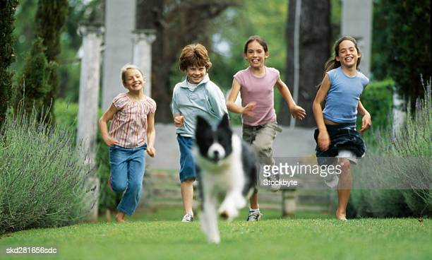 Four children and dog running
