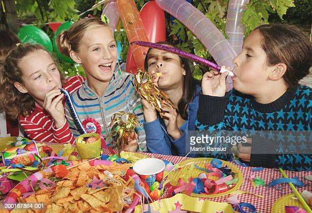 Four children (9-11) at birthday party with blowers, outdoors