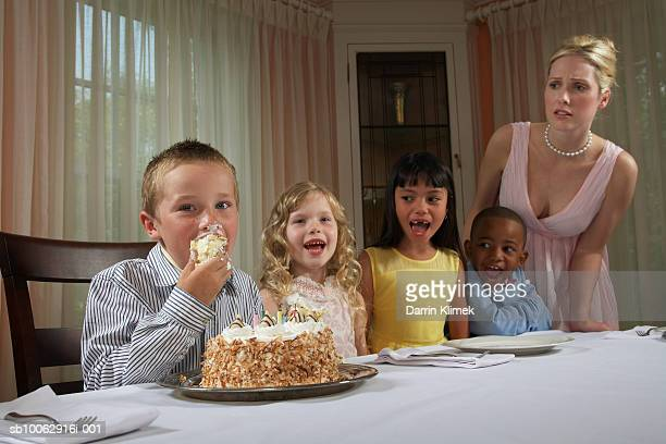 Four children (5-8 years) at table, boy eating birthday cake with hands