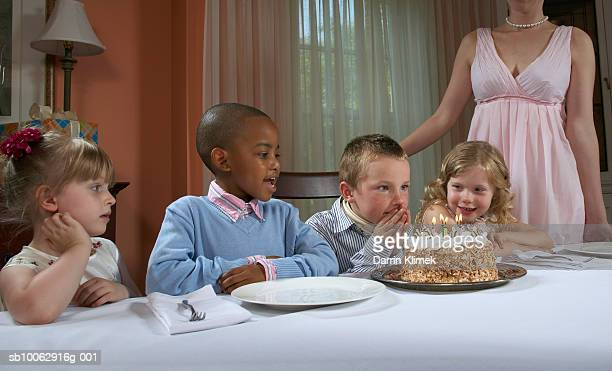 four children (4-7 years) at table in dining room, looking at birthday cake, mother in background - 25 29 years stock pictures, royalty-free photos & images