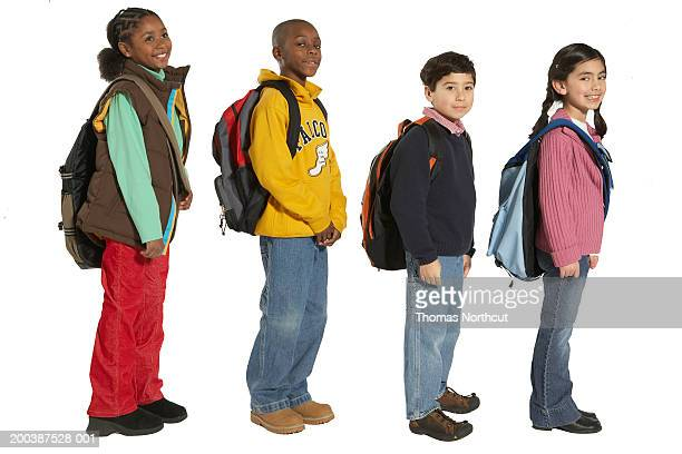 Four children (7-9) carrying backpacks and shoulder bags, side view