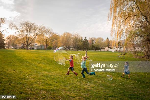 four children chasing giant soap bubbles in a public park - park stock-fotos und bilder