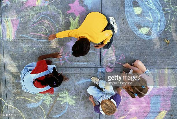 Four children (7-10) drawing with chalk on pavement, overhead view