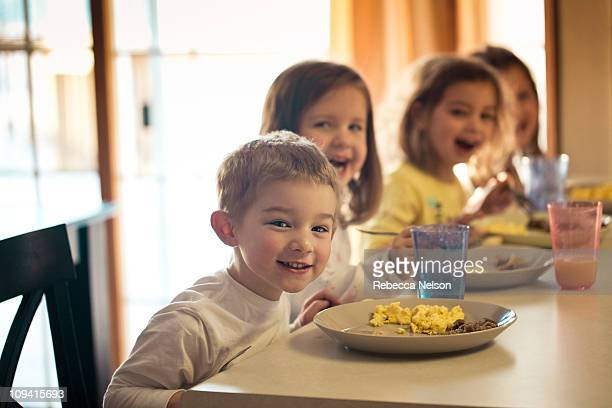 Four children eating breakfast at counter