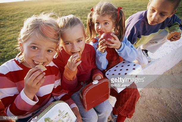 Four children (4-7) eating snack from lunch boxes, outdoors