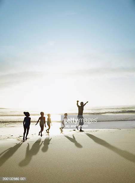 four children (4-7) following man on beach, sunset, silhouette - mid distance stock pictures, royalty-free photos & images
