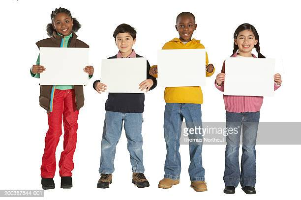 Four children (7-9) holding blank signs, smiling, portrait