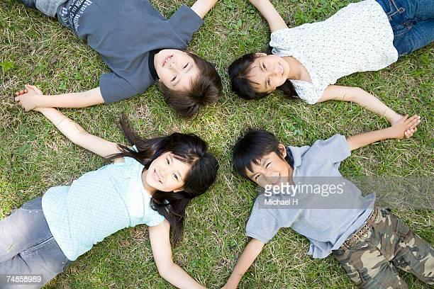 Four children (5-9) holding hands, lying on grass, portrait