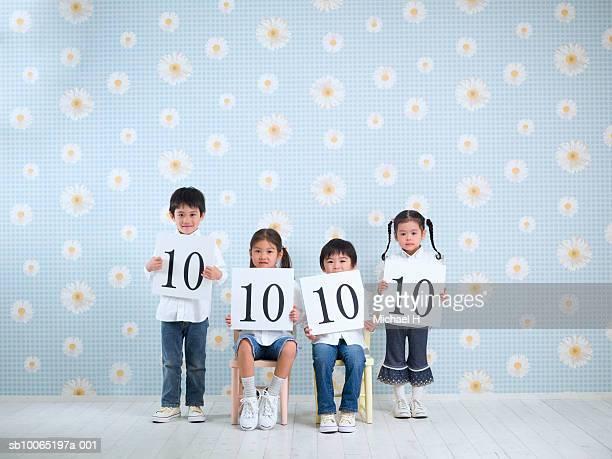Four children (4-5 years) holding score boards, studio shot, portrait