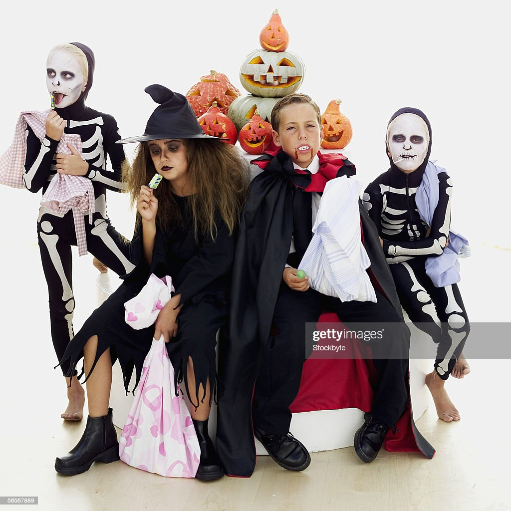 four children in halloween costumes sitting around carved pumpkins : Stock Photo