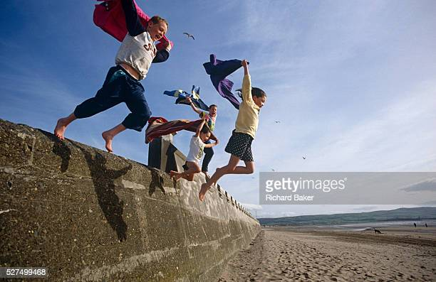 Four children leap out into the wide blue yonder on a beach in Whitley Bay England Jumping at a height from a sea defence wall the kids all hold...